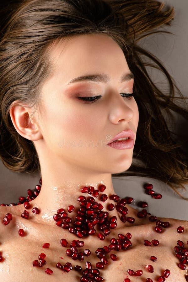 Vrouwelijk donkerbruin meisje met mooie make-up en granaatappelzaden stock fotografie