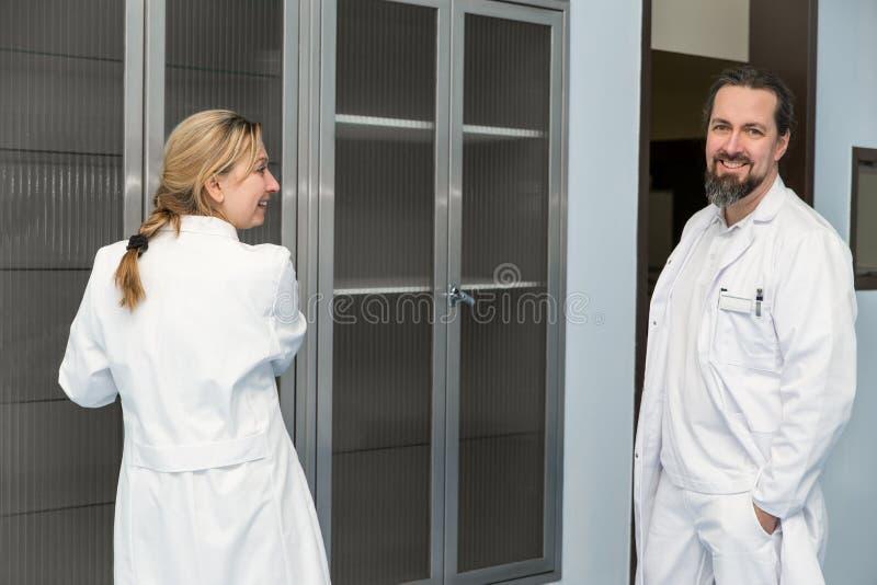 Vrouwelijk en mannelijk arts of geneeskundepersoneel voor een geneeskunde royalty-vrije stock afbeeldingen
