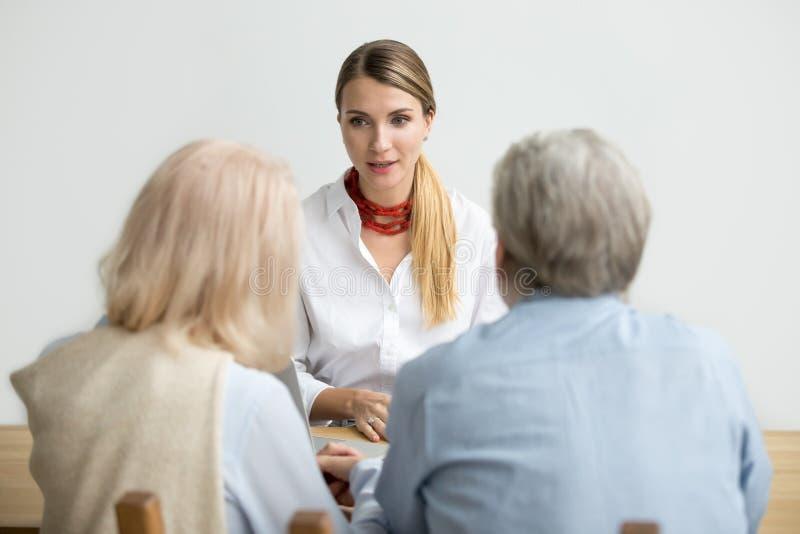 Vrouwelijk financieel adviseurs sprekend raadplegend hoger oud paar a royalty-vrije stock fotografie