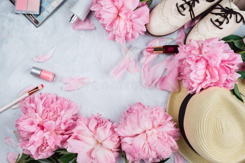 Vrouwelijk flatlay model met hoed, roze pioenen, schoonheidsmiddelen en witte brogue schoenen stock afbeeldingen