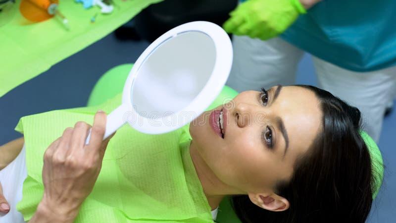 Vrouwelijk geduldig het controleren resultaat van nieuwe dichtingsproductplaatsing, kosmetische tandheelkunde stock foto
