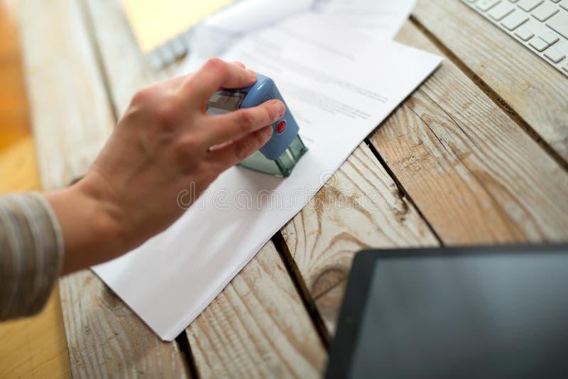 Vrouwelijk hand het stempelen document stock afbeelding