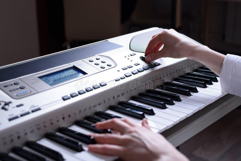Vrouwelijk handenopstelling en spel op een elektronische piano, achtermening royalty-vrije stock fotografie