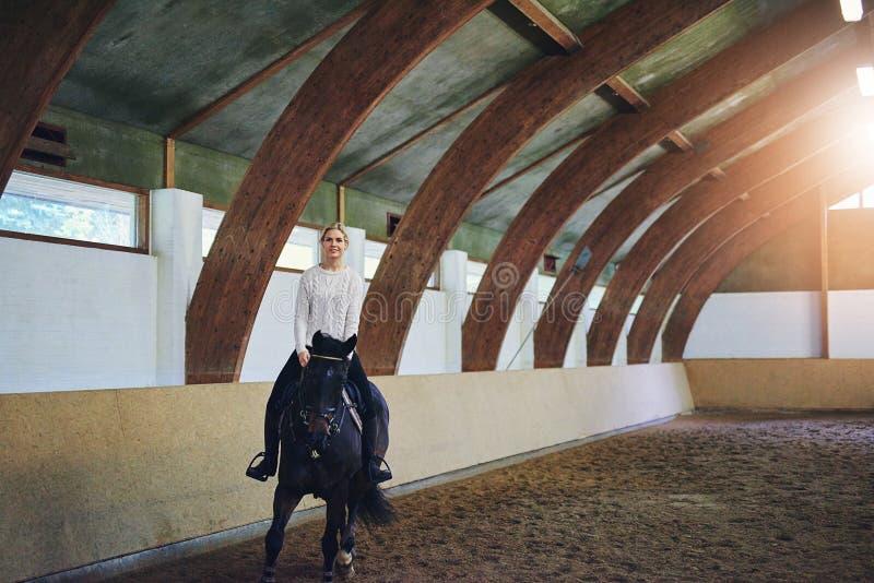 Vrouwelijk het berijden paard in binnen berijdende zaal stock fotografie