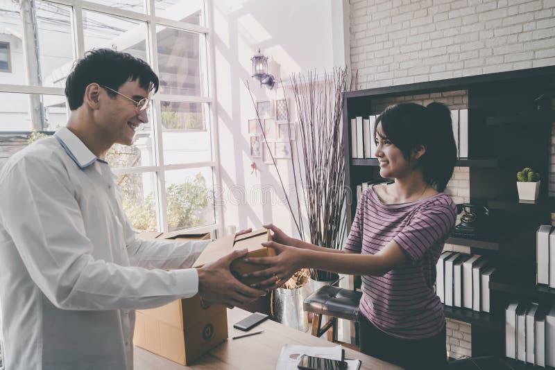 Vrouwelijk huis bedrijfseigenaar behandelend pakket aan klant royalty-vrije stock fotografie