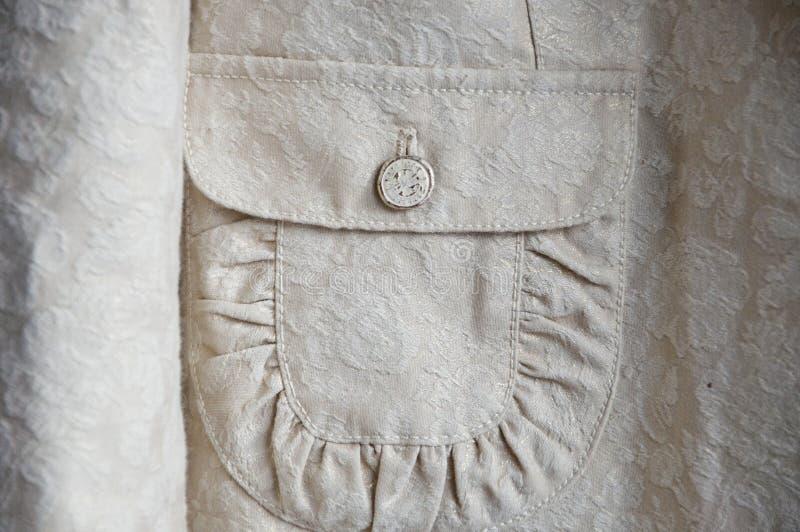 Vrouwelijk jasjedeel met knoop op zak stock foto's