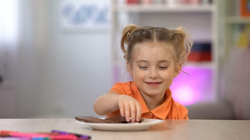 Vrouwelijk jong geitje die in het geheim chocolade van witte plaat op lijst, suikeroverdosis nemen stock afbeeldingen