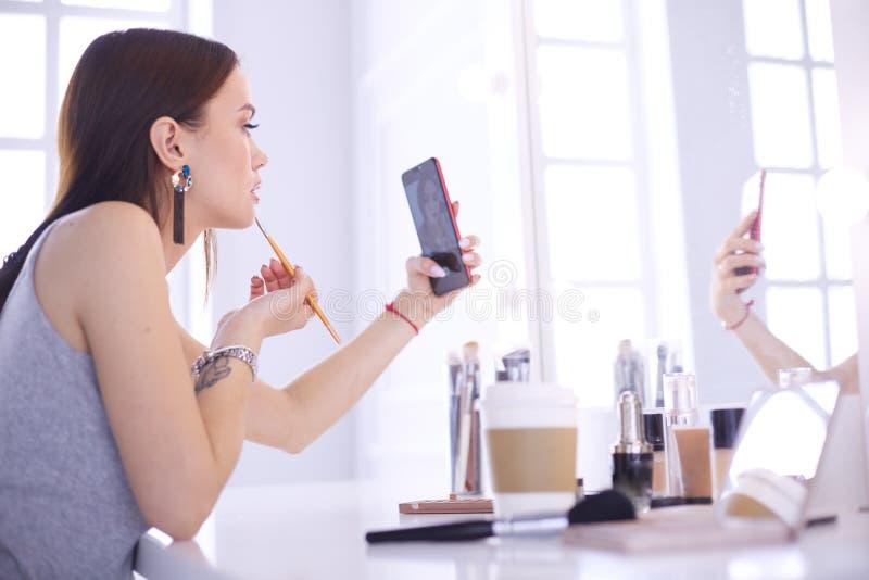 Vrouwelijk jong mooi meisje met krullend haar en samenstelling de mooie vrouw maakt zelf-portret zelf telefonisch royalty-vrije stock fotografie