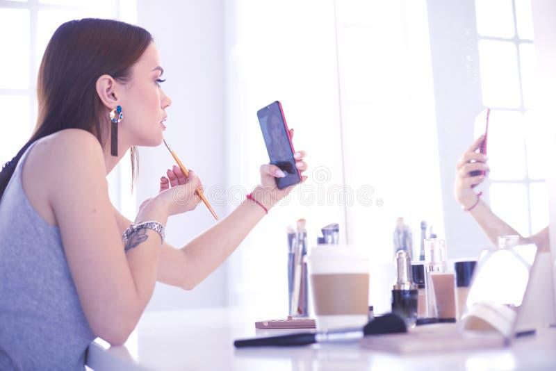 Vrouwelijk jong mooi meisje met krullend haar en samenstelling de mooie vrouw maakt zelf-portret zelf telefonisch stock afbeeldingen