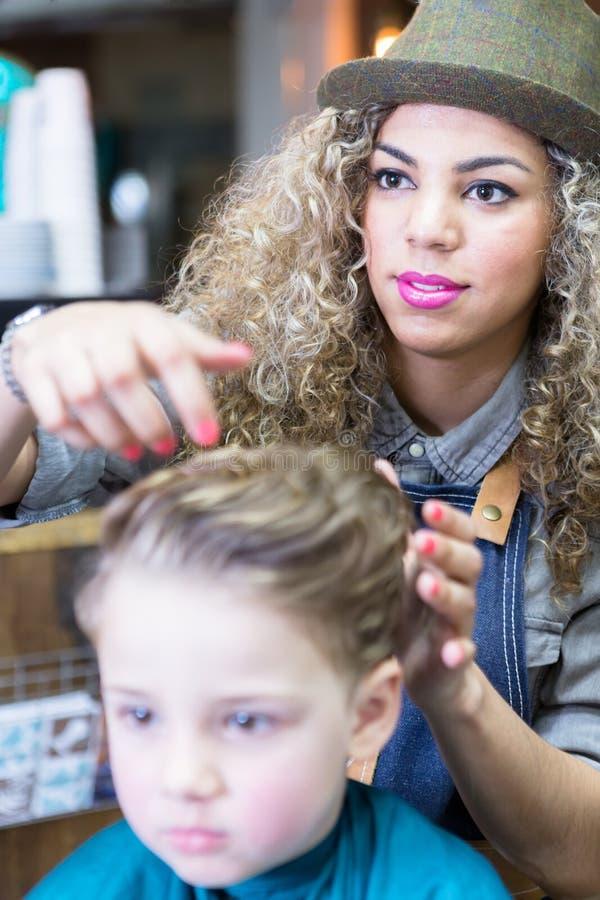 Vrouwelijk kapper het plaatsen jongenshaar royalty-vrije stock afbeeldingen