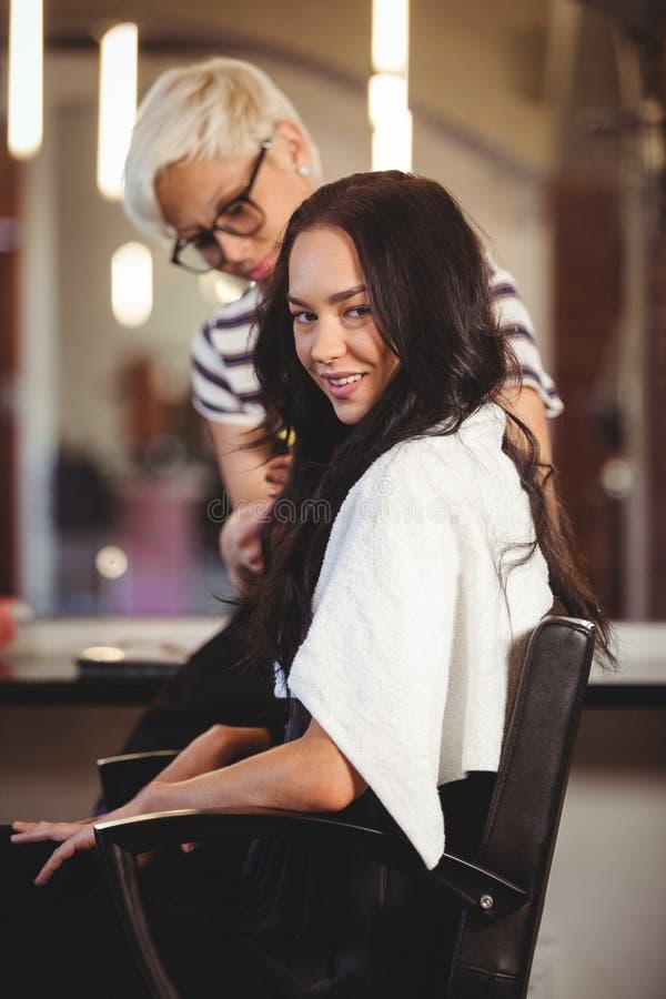 Vrouwelijk kapper het stileren klantenhaar stock afbeelding