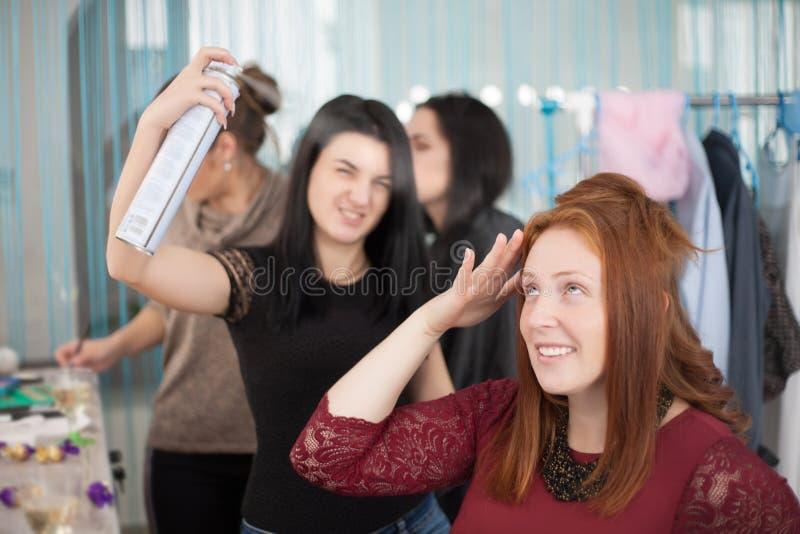 Vrouwelijk kapper het stileren klantenhaar bij een salon stock foto