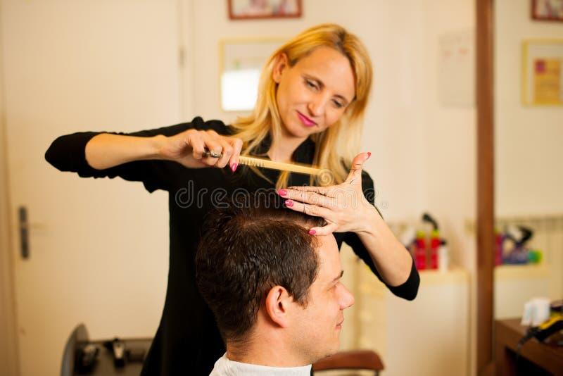 Vrouwelijk kapper scherp haar van glimlachende mensencliënt bij schoonheid stock foto's