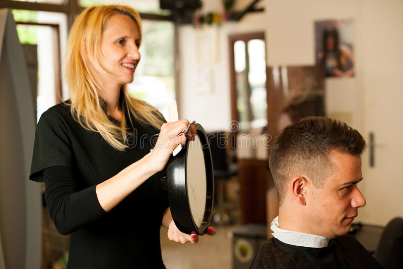 Vrouwelijk kapper scherp haar van glimlachende mensencliënt bij schoonheid stock fotografie