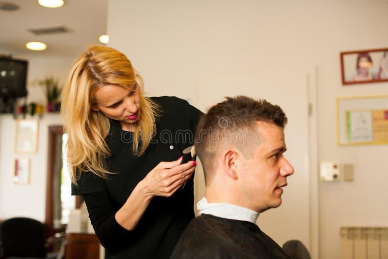 Vrouwelijk kapper scherp haar van glimlachende mensencliënt bij schoonheid royalty-vrije stock foto