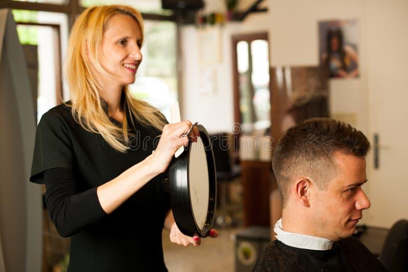 Vrouwelijk kapper scherp haar van glimlachende mensencliënt bij schoonheid royalty-vrije stock foto's