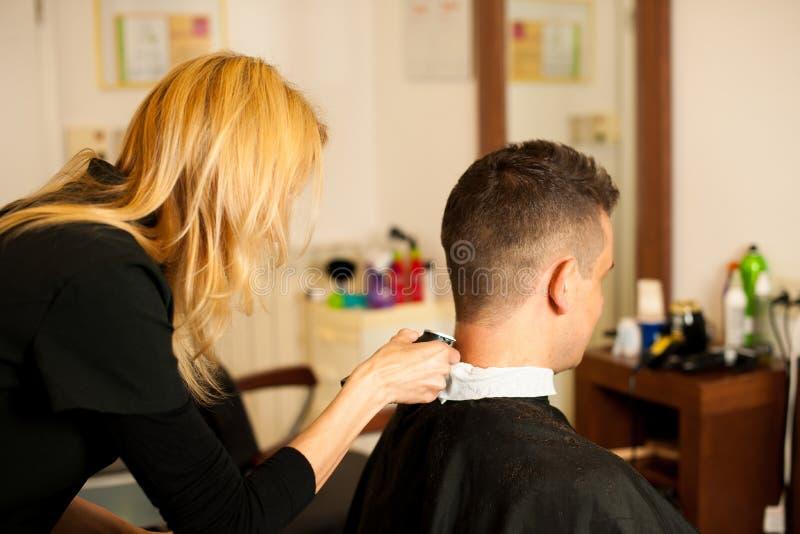 Vrouwelijk kapper scherp haar van glimlachende mensencliënt bij schoonheid royalty-vrije stock afbeelding
