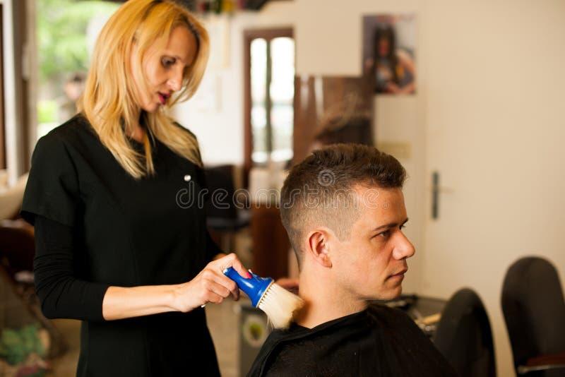 Vrouwelijk kapper scherp haar van glimlachende mensencliënt bij schoonheid royalty-vrije stock afbeeldingen