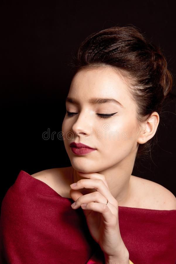 Vrouwelijk kapsel middelgroot broodje met de bruine rode lippen van de haarsamenstelling en zwarte pijl perfecte huid stock foto's