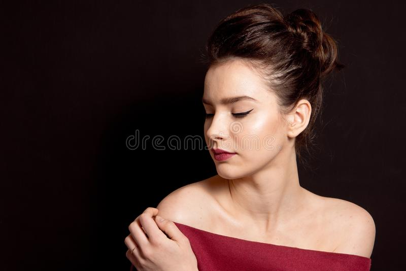 Vrouwelijk kapsel middelgroot broodje met de bruine rode lippen van de haarsamenstelling en zwarte pijl perfecte huid royalty-vrije stock afbeelding