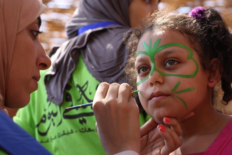 Vrouwelijk leraar het schilderen meisjesgezicht in vlindervorm in speelplaats stock fotografie