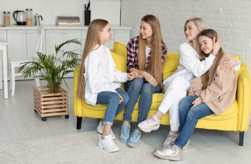 Vrouwelijk lesbisch paar met hun aantrekkelijke daughers thuis Lesbische familie die in vrijetijdskleding op gele bank zitten royalty-vrije stock afbeelding