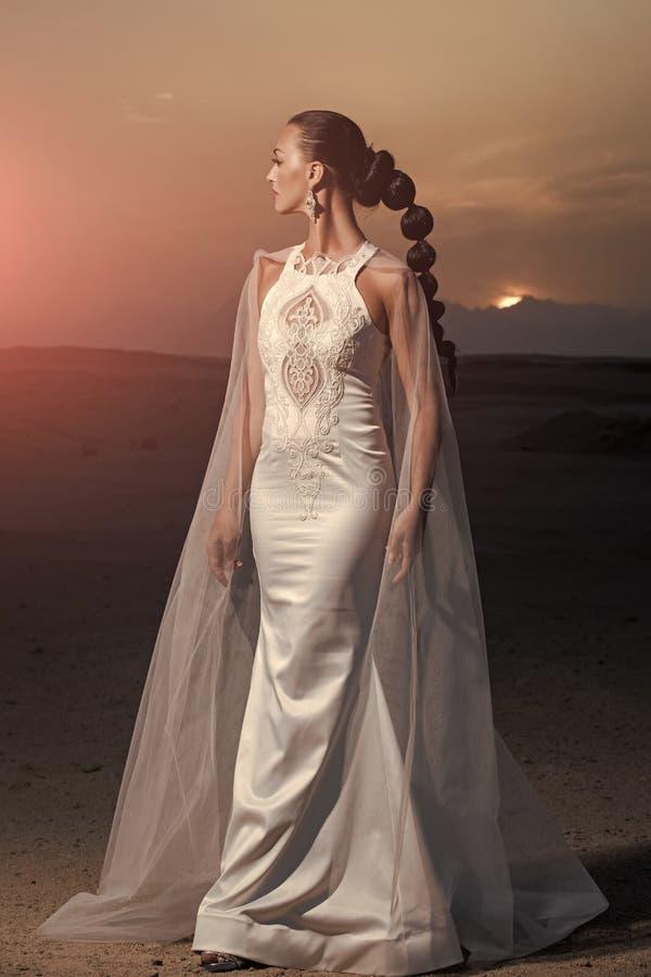 Vrouwelijk manier, schoonheid en reclameconcept Meisje het stellen op woestijnzonsondergang royalty-vrije stock afbeelding