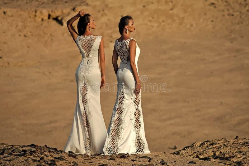 Vrouwelijk manierconcept Twee vrouwen in witte kleding, achtermening, die in woestijn stellen stock foto
