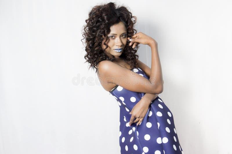 Vrouwelijk model die een blauwe en witte polka gestippelde kleding dragen royalty-vrije stock afbeelding