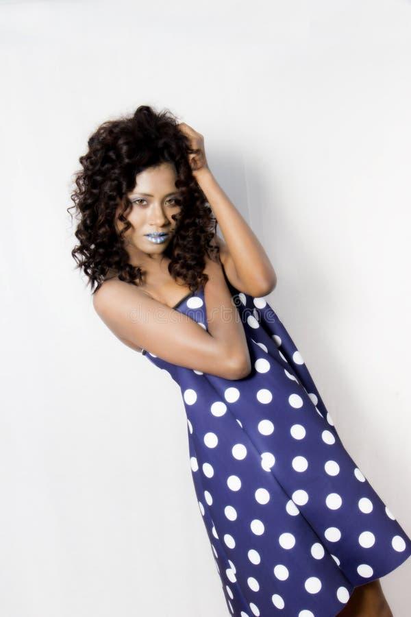 Vrouwelijk model die een blauwe en witte polka gestippelde kleding dragen stock afbeelding