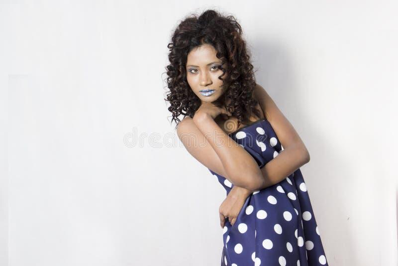 Vrouwelijk model die een blauwe en witte polka gestippelde kleding dragen stock foto