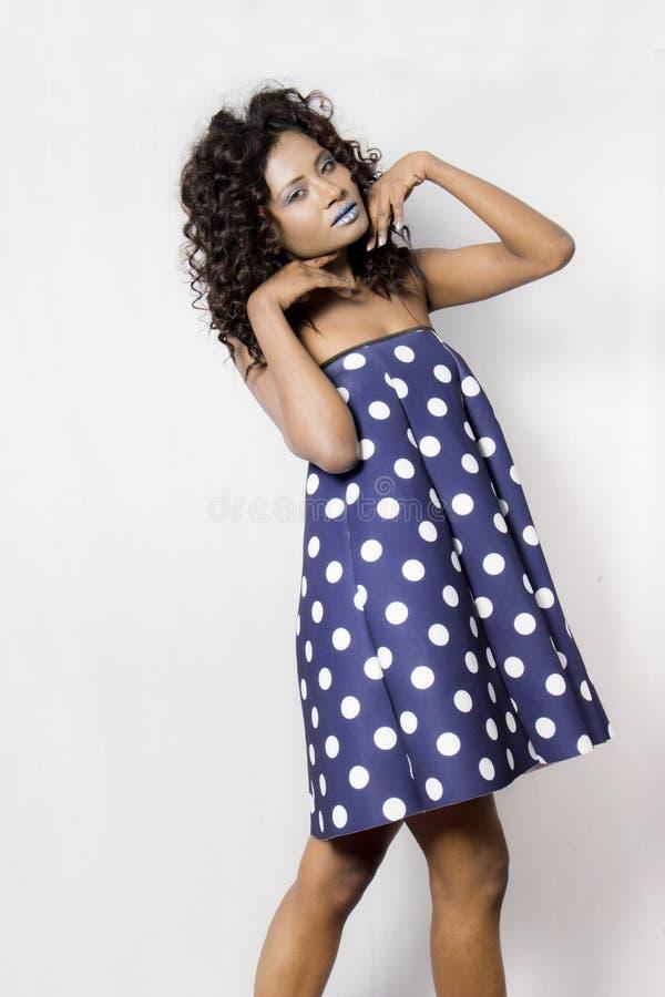 Vrouwelijk model die een blauwe en witte polka gestippelde kleding dragen stock afbeeldingen