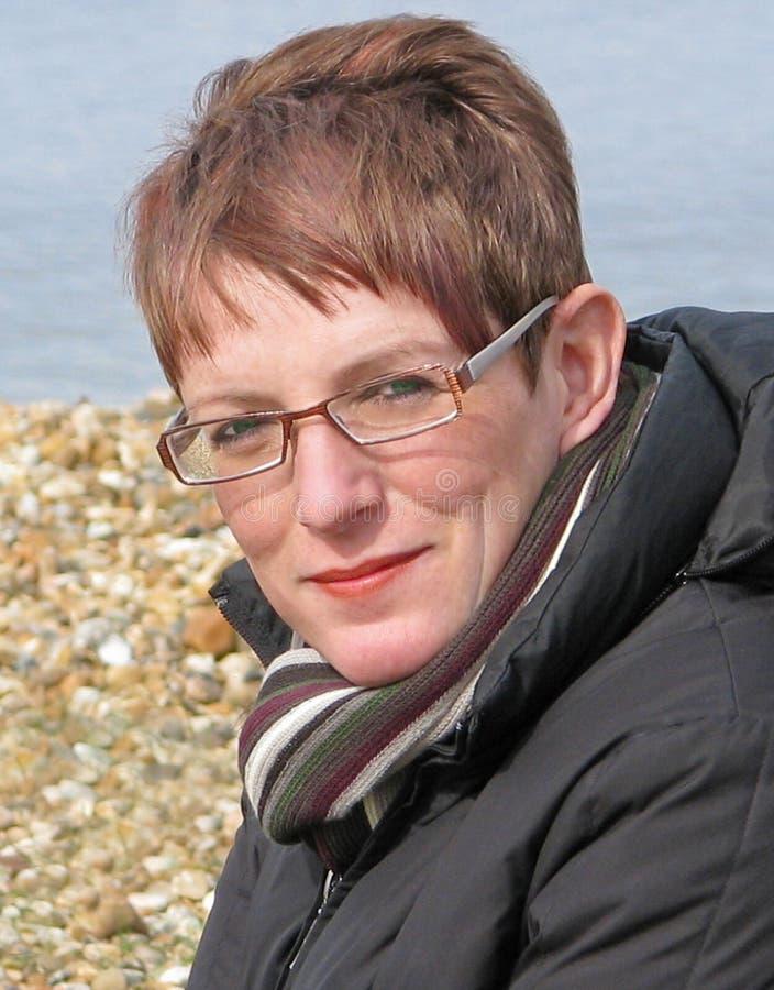 Vrouwelijk model met glazen die op strand stellen stock fotografie