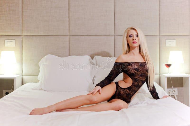 Vrouwelijk model op wit zacht bed stock afbeeldingen