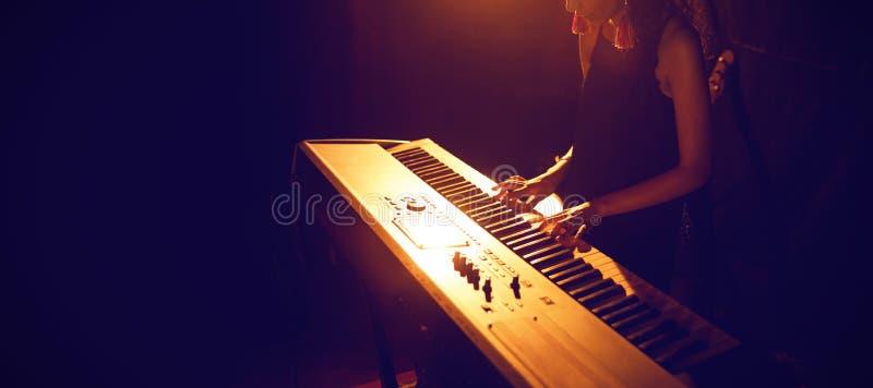 Vrouwelijk musicus het spelen pianotoetsenbord in verlichte club royalty-vrije stock afbeelding
