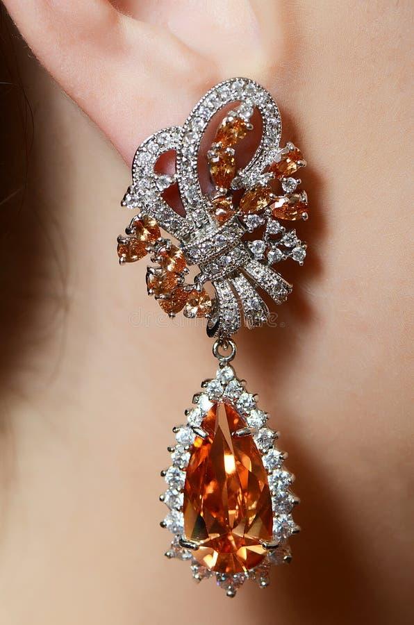 Vrouwelijk oor in juwelenoorringen stock foto's