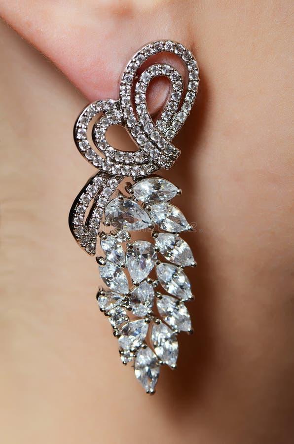 Vrouwelijk oor in juwelenoorringen royalty-vrije stock afbeeldingen