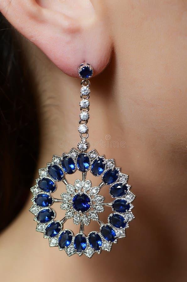 Vrouwelijk oor in juwelenoorringen royalty-vrije stock foto's
