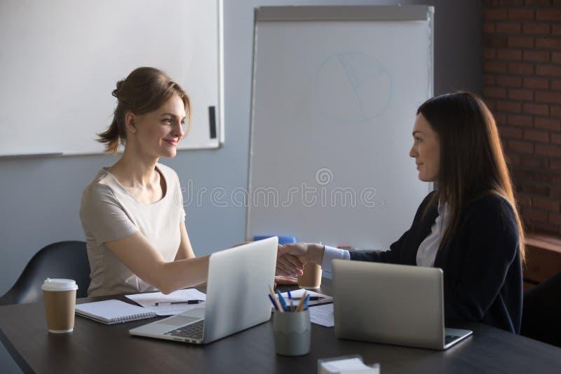 Vrouwelijk partnershandenschudden na succesvolle negotiatio stock foto's