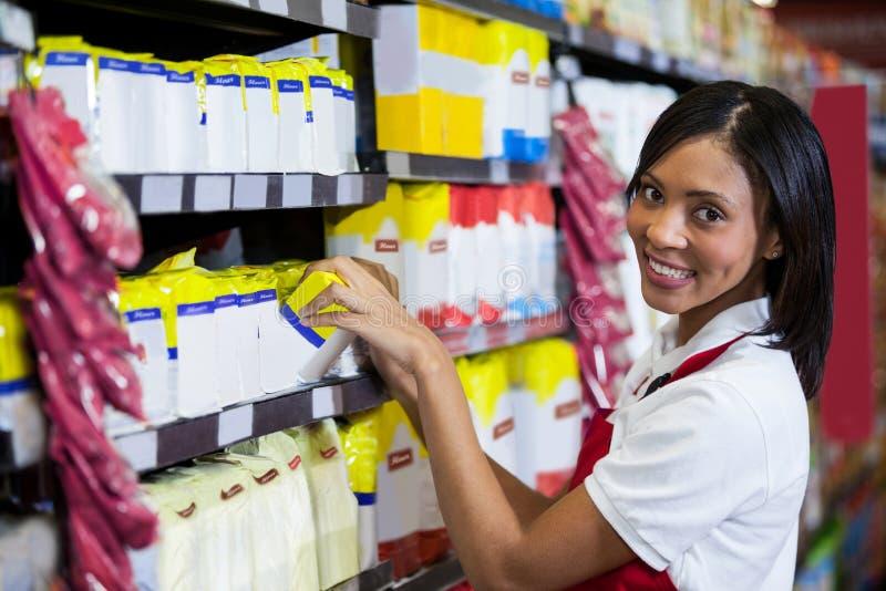 Vrouwelijk personeel die goederen in kruidenierswinkelsectie schikken royalty-vrije stock foto's
