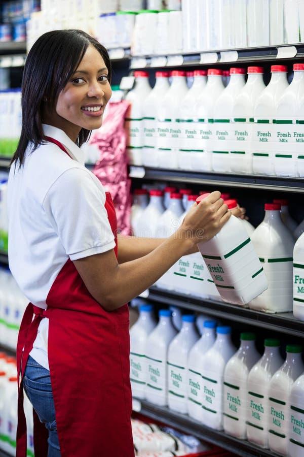 Vrouwelijk personeel die melkfles in plank schikken royalty-vrije stock foto's