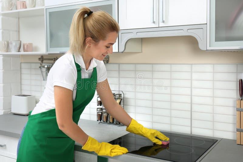 Vrouwelijk portier schoonmakend fornuis met spons stock foto