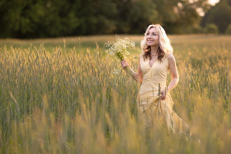 Vrouwelijk portret in openlucht een vrouw in een strohoed op een bloemgebied met een boeket van wilde bloemen De zomer in het lan royalty-vrije stock foto