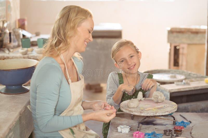 Vrouwelijk pottenbakker en meisje die in workshop werken stock foto