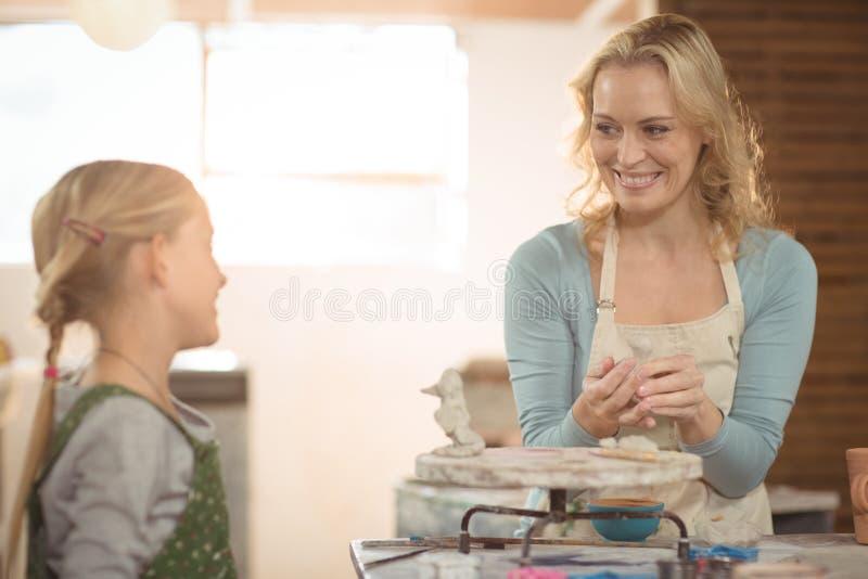 Vrouwelijk pottenbakker en meisje die in workshop werken royalty-vrije stock afbeeldingen