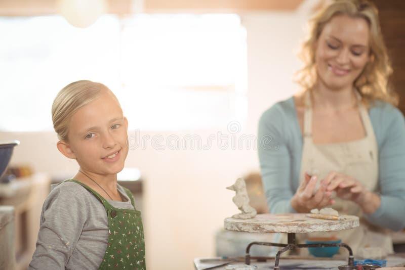 Vrouwelijk pottenbakker en meisje die in workshop werken royalty-vrije stock fotografie