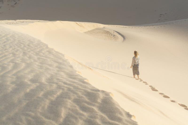 Vrouwelijk silhouet die in de duinen van het woestijnzand van Mui Ne, Vietnam lopen royalty-vrije stock fotografie