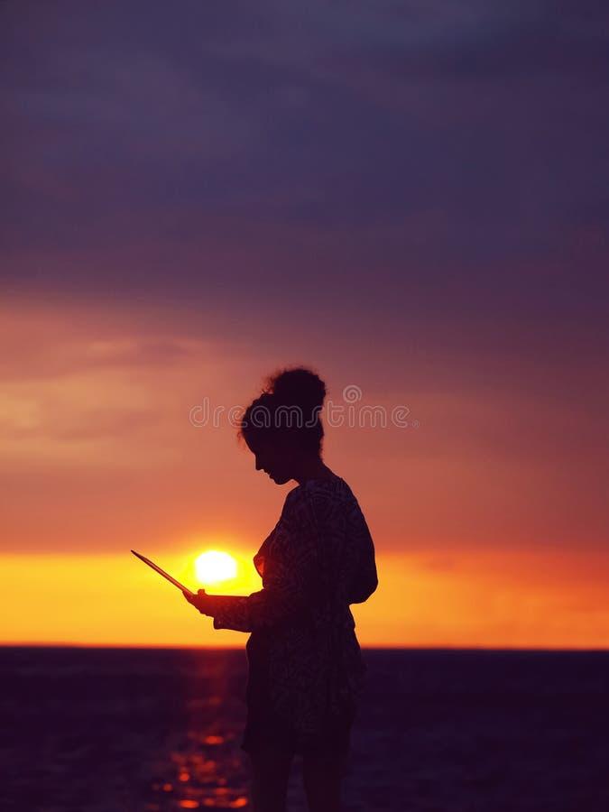 Vrouwelijk silhouet met laptop op zonsondergang stock afbeelding