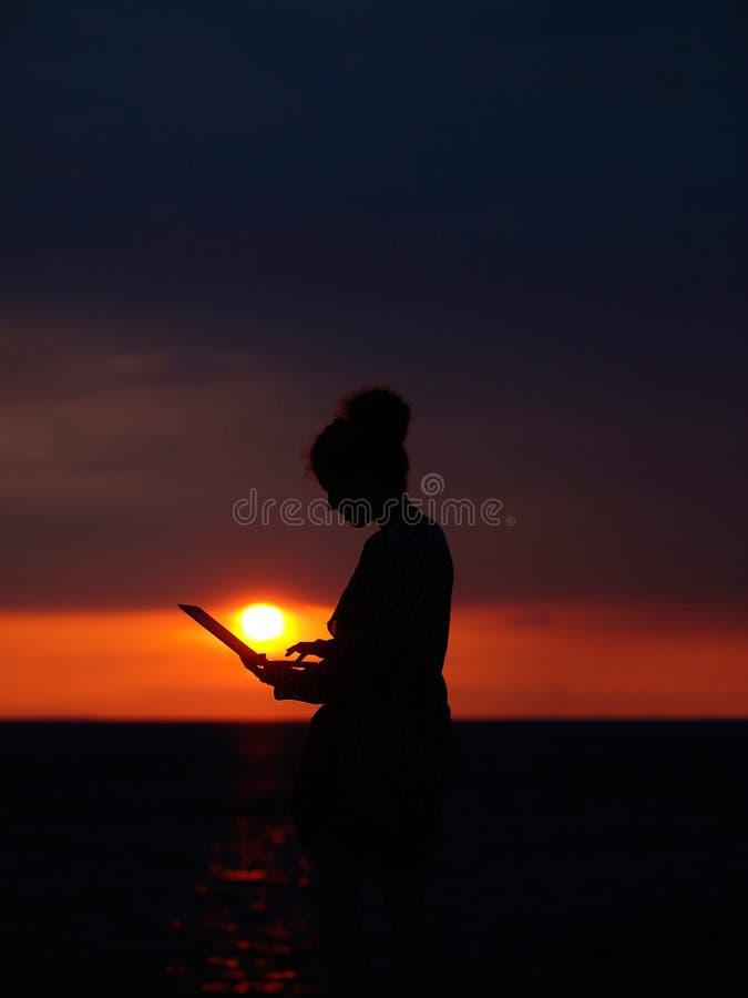 Vrouwelijk silhouet met laptop op zonsondergang stock fotografie