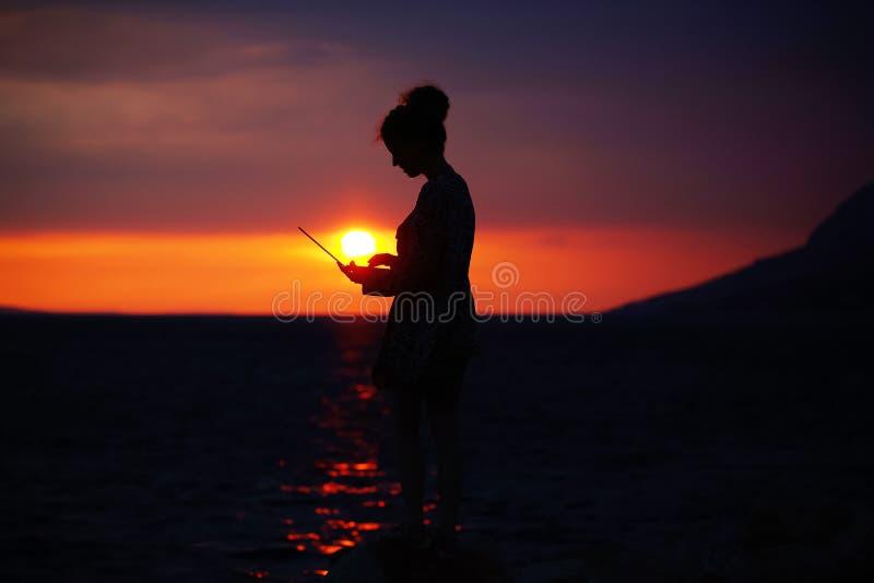 Vrouwelijk silhouet met laptop op zonsondergang royalty-vrije stock foto's